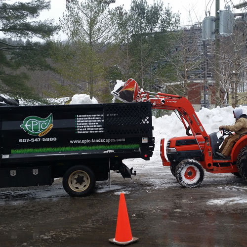 Using a tractor and dump truck to remove large piles of snow.